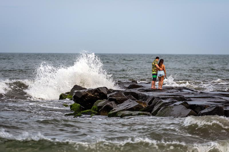ATLANTIC CITY, NEW JERSEY - JUNE 18, 2019:  A romantic couple of young people on a stone mole on the ocean coast royalty free stock image
