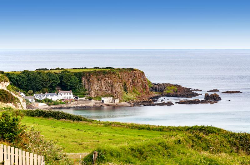 Steep cliff at the Atlantic coast in Northern Ireland, UK. Atlantic coast with a steep rocky cliff and houses in County Antrim, Northern Ireland, UK royalty free stock photo