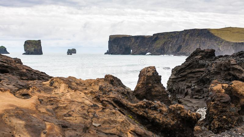 Atlantic ocean coast and view of Dyrholaey. Travel to Iceland - Atlantic ocean volcanic coast and view of Dyrholaey promontory near Vik I Myrdal village on stock images