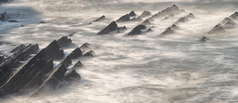 Jagged rocks in Atlantic ocean. Abbey river beach, Hartland, Devon. Long exposure of the Atlantic ocean waves, with rows of jagged teethlike rocks, ominously royalty free stock photos