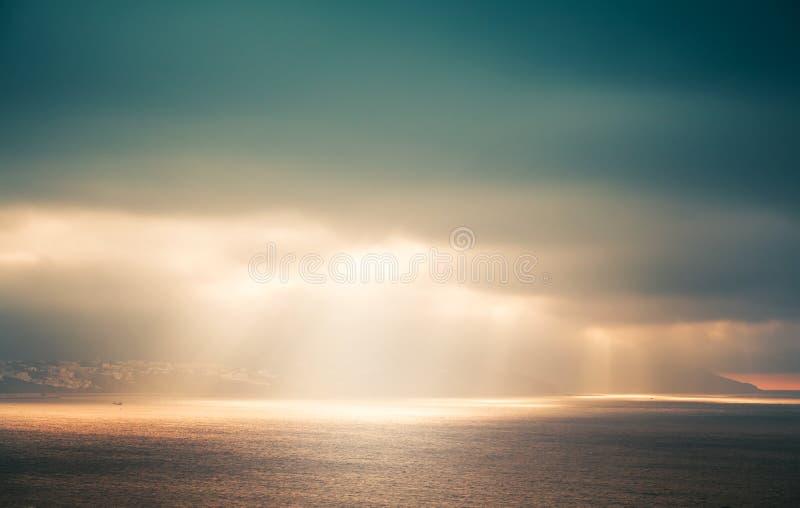 Atlantic ocean landscape, evening sunlight in sky. Atlantic ocean landscape, evening sunlight goes through dark cloudy sky. Retro style, colorful tonal stock image