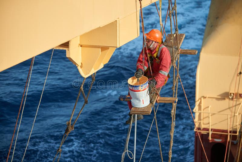Ships crew working aloft and painting cranes. Atlantic Ocean, Open Sea - Circa March 2019: International Ships Crew Performing working aloft, crane painting royalty free stock image