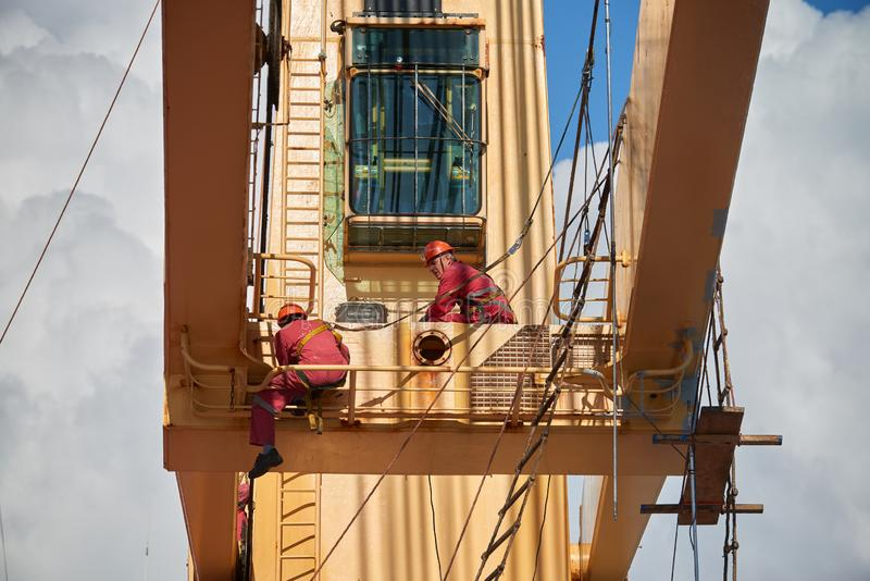 Ships crew working aloft and painting cranes. Atlantic Ocean, Open Sea - Circa March 2019: International Ships Crew Performing working aloft, crane painting royalty free stock photo