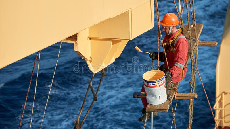 Ships crew working aloft and painting cranes. Atlantic Ocean, Open Sea - Circa March 2019: International Ships Crew Performing working aloft, crane painting stock image