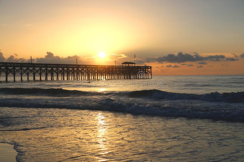 Atlantic ocean sunrise. Atlantic ocean landscape with first rays of rising sun over the ocean beach with wooden pier stock images