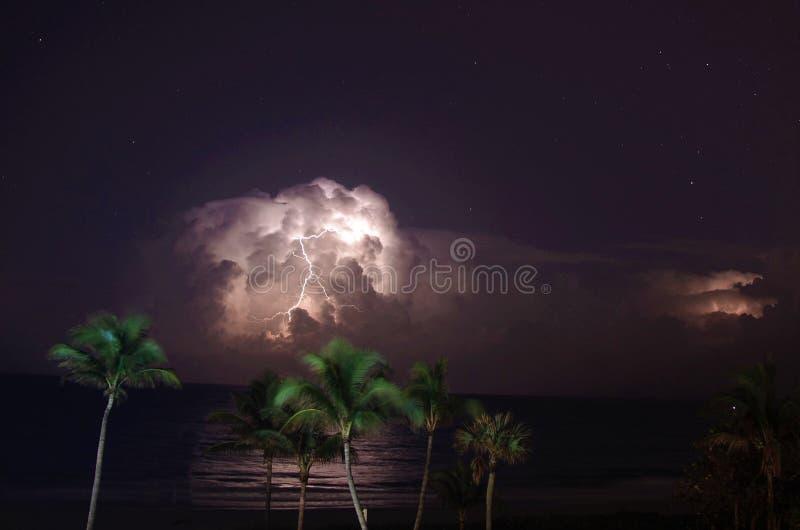 An Atlantic Ocean thunderstorm lights up the dark beach night with its lightning display stock image
