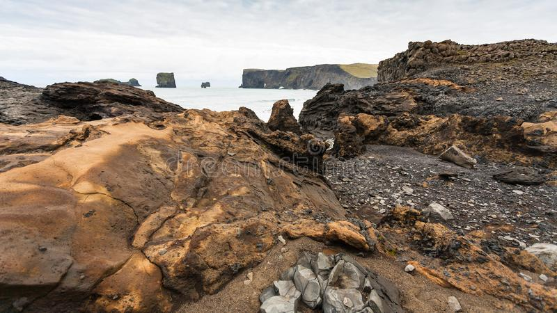 Atlantic volcanic beach and view of Dyrholaey. Travel to Iceland - Atlantic ocean volcanic beach and view of Dyrholaey promontory near Vik I Myrdal village on stock images