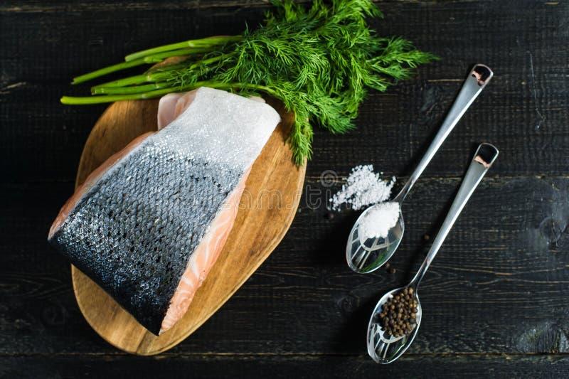 Atlantische ruwe zalm, lapje vlees en peterselietwijg op zwarte houten achtergrond stock fotografie