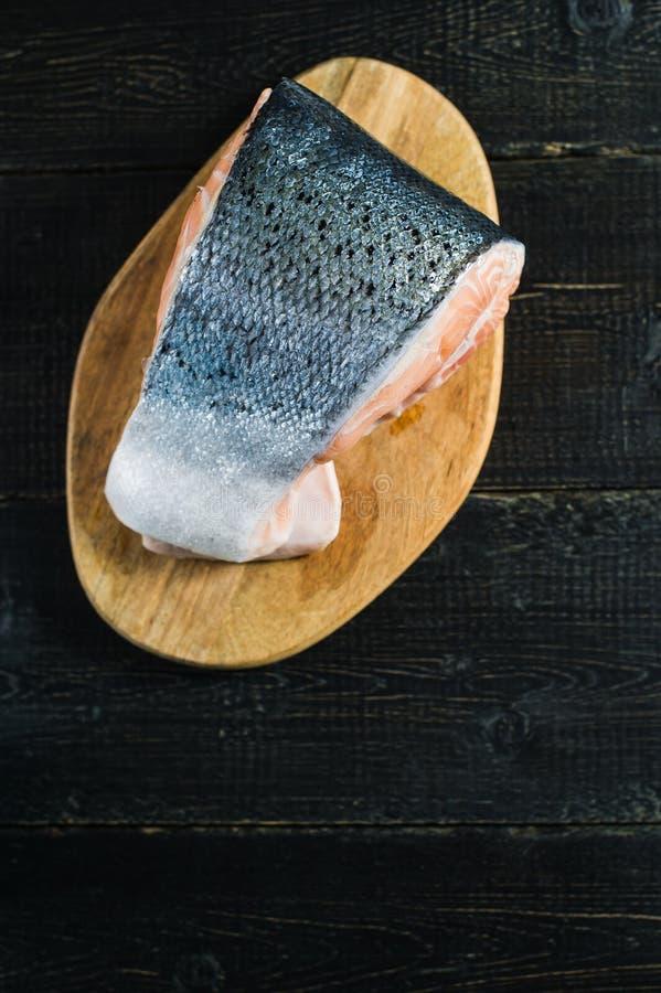 Atlantische ruwe zalm, lapje vlees op zwarte houten achtergrond stock afbeeldingen