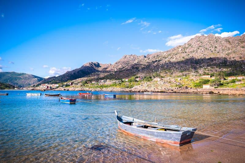 Atlantisk kust för skönhet med fiskebåtar, stranden, havet, byn, berg och himmel med moln Galicia Spanien fotografering för bildbyråer