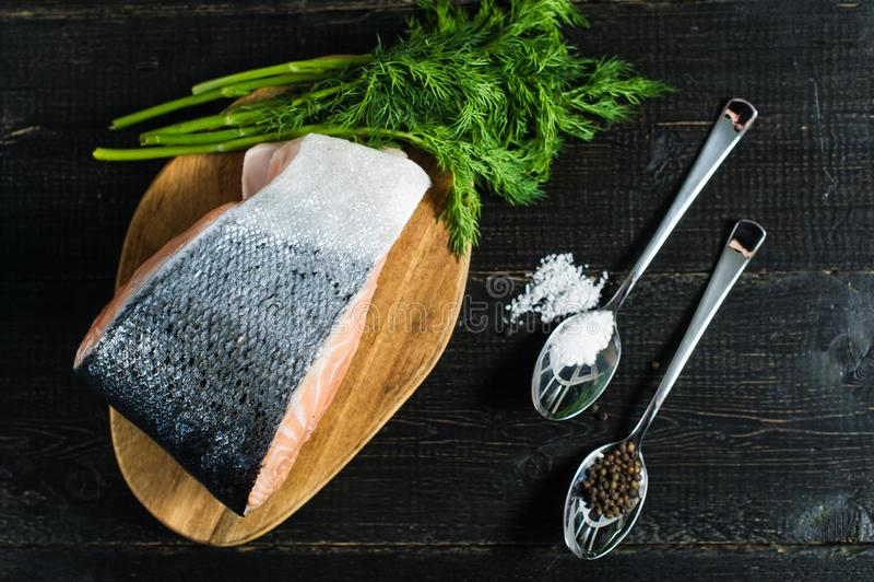 Atlantycki surowy łososia, stku i pietruszki sprig na czarnym drewnianym tle, fotografia stock