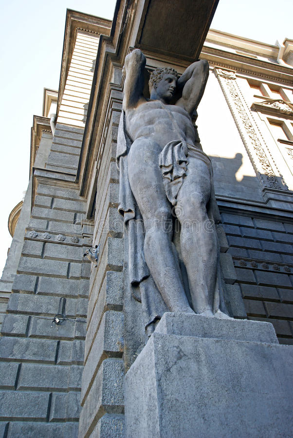 Atlas at the main entrance to the building holding portal beam. Sculptural support, telamon royalty free stock photos