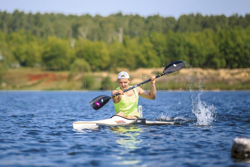 Atleet bij het roeien van kajak op meer, nevel van water onder peddel royalty-vrije stock fotografie