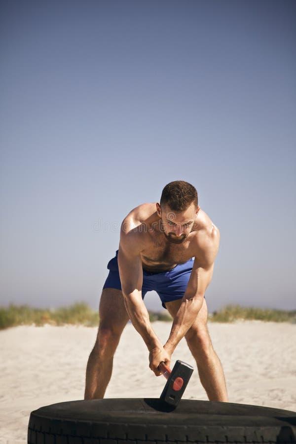 Atleet die crossfit hamer opleiding op strand doen stock afbeelding