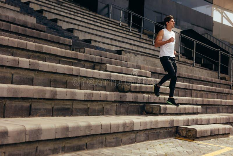 Atleet die de treden van een stadiontribune reduceren stock foto