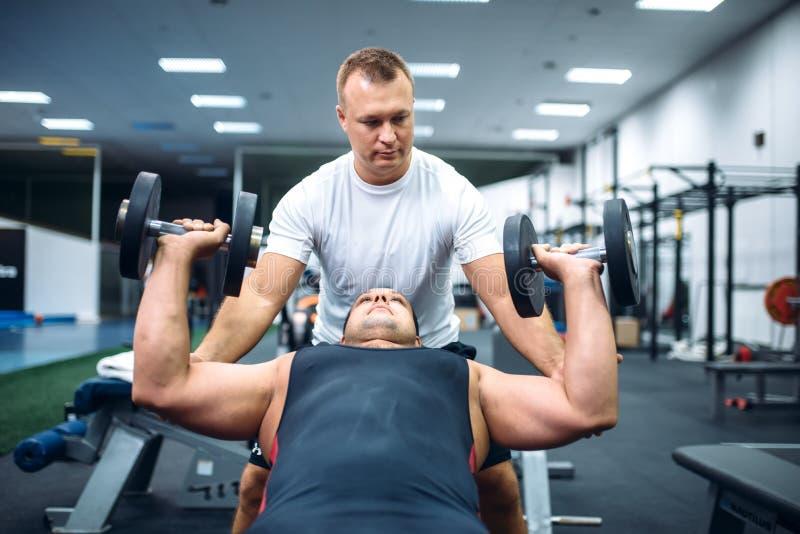 Atleet die oefening doen onder instructeurscontrole stock afbeelding