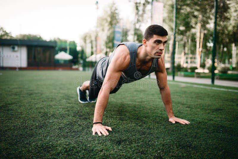 Atleet die opdrukoefeningoefening op openluchttraining doen royalty-vrije stock fotografie