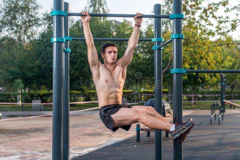 Atleet het hangen op geschiktheidspost die benen uitvoeren heft op Kernkruis die uitwerkend abs spieren opleiden stock afbeelding
