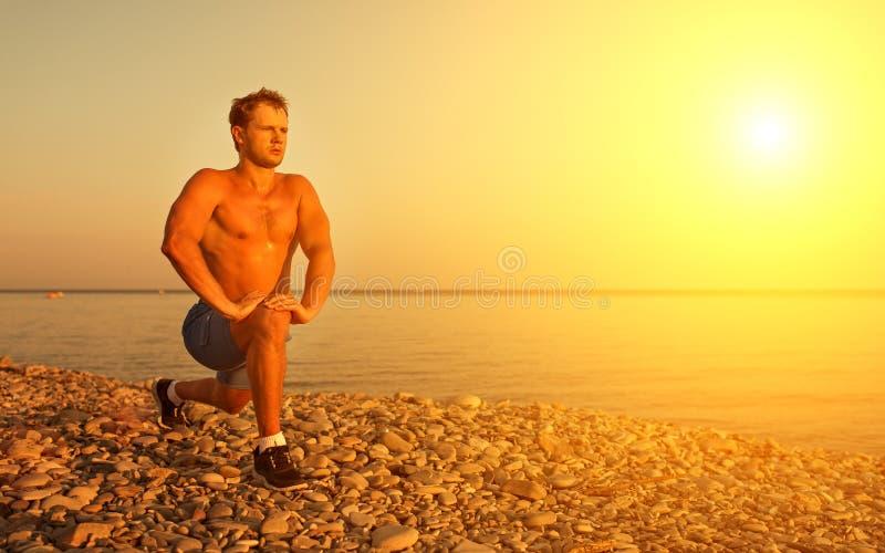 Atleet het praktizeren, het spelen sporten op strand stock fotografie