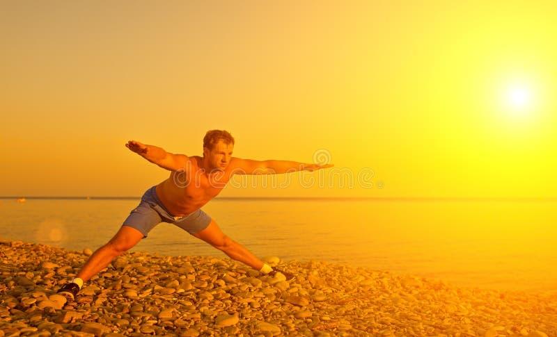 Atleet het praktizeren, yoga op strand bij zonnen stock foto's