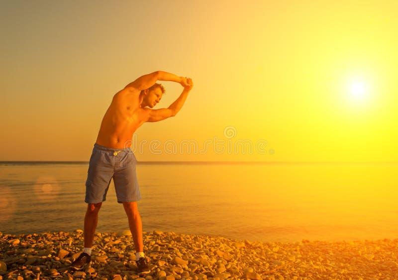 Atleet, het spelen sporten en yoga op strand royalty-vrije stock foto's