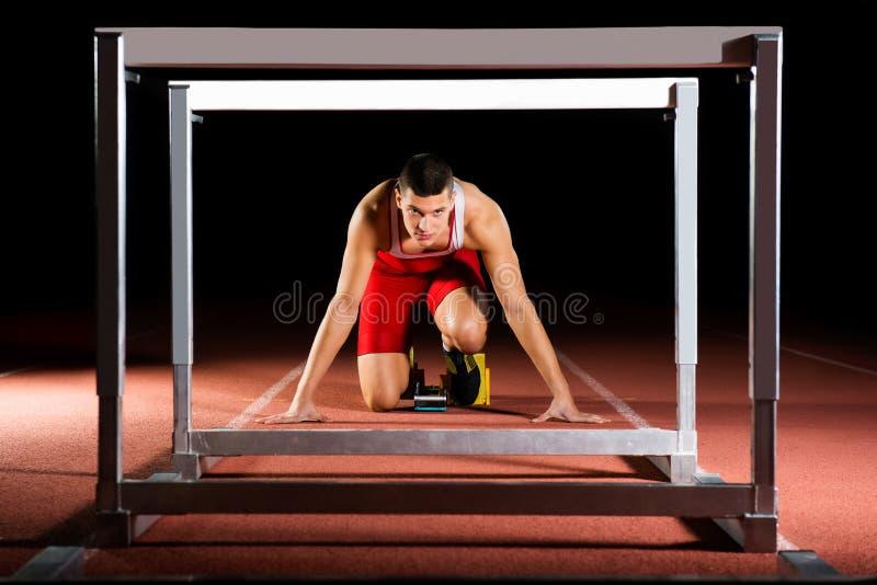 Atleet op de startblokken met hindernissen stock foto