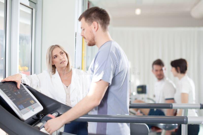 Atleet op een tredmolen met fysiotherapeut arts stock foto's