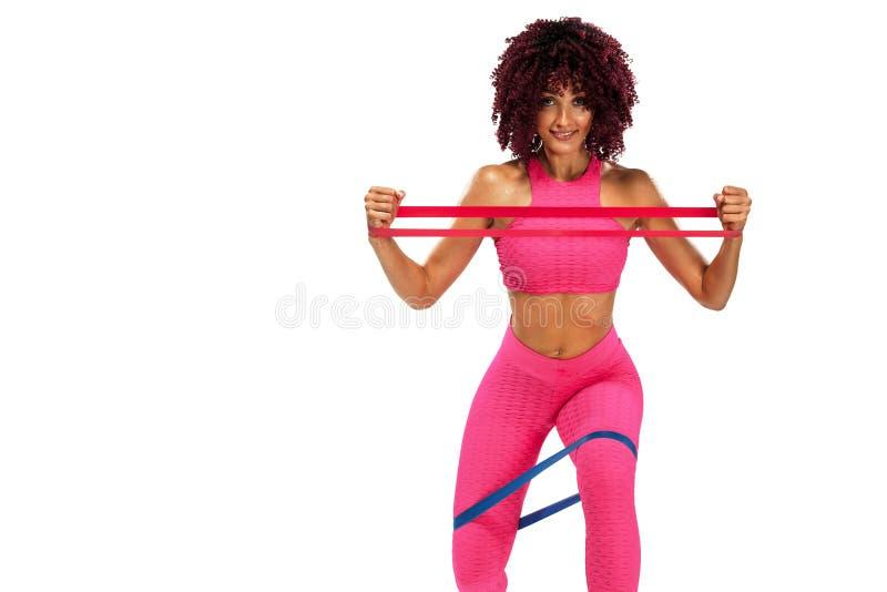 Atleta adatto della donna di sport dei giovani muscolari in abiti sportivi rosa con le bande o estensore in palestra Copi lo spaz immagine stock