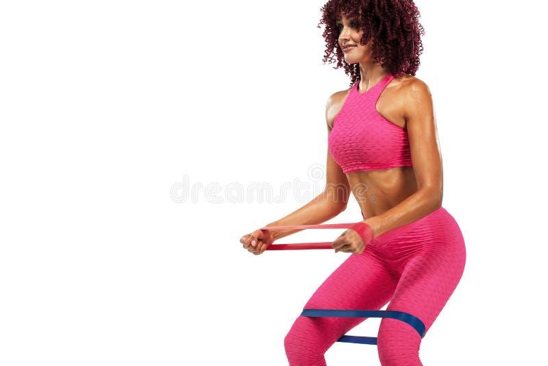 Atleta adatto della donna di sport dei giovani muscolari in abiti sportivi rosa con le bande o estensore in palestra Copi lo spaz fotografia stock