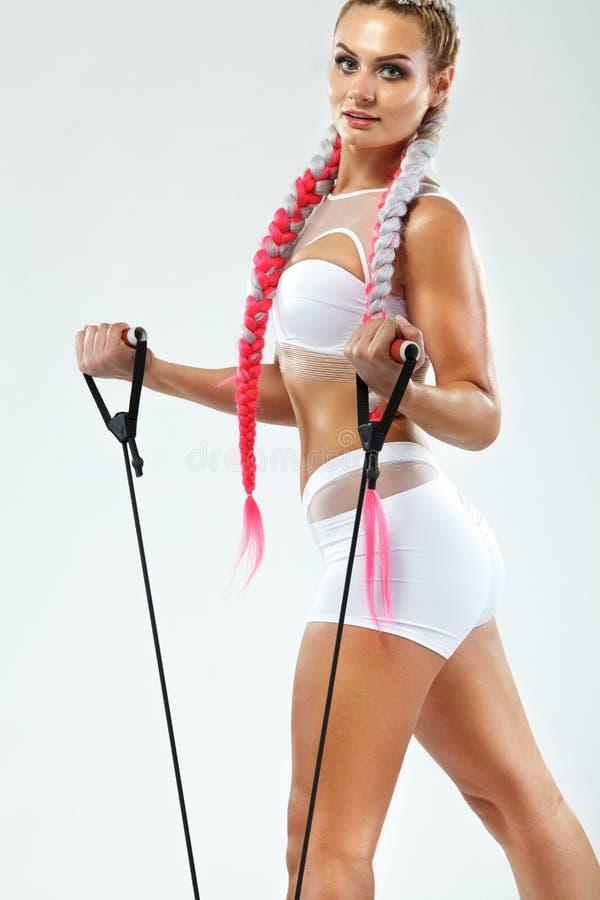 Atleta adatto della donna di sport dei giovani muscolari in abiti sportivi rosa con le bande o estensore in palestra Copi lo spaz fotografia stock libera da diritti