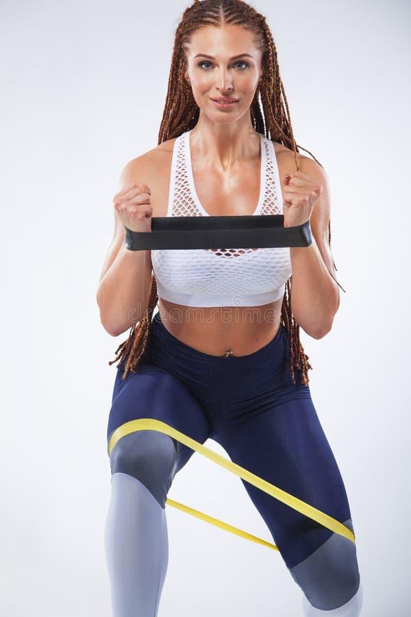 Atleta adatto della donna di sport dei giovani muscolari Allenamento con le bande o l'estensore in palestra Copi lo spazio per gl fotografia stock libera da diritti