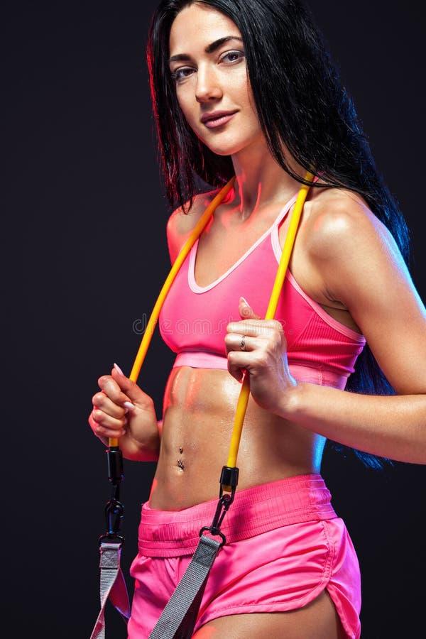 Atleta adatto della donna di sport dei giovani muscolari Allenamento con le bande o l'estensore in palestra su fondo nero Forte a fotografia stock