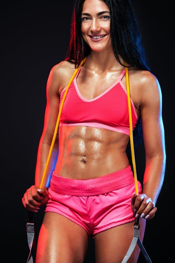 Atleta adatto della donna di sport dei giovani muscolari Allenamento con le bande o l'estensore in palestra su fondo nero Forte a fotografia stock libera da diritti