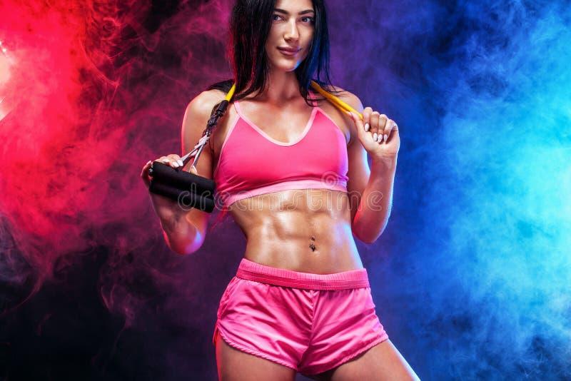 Atleta adatto della donna di sport dei giovani muscolari Allenamento con le bande o l'estensore in palestra su fondo nero con il  immagini stock