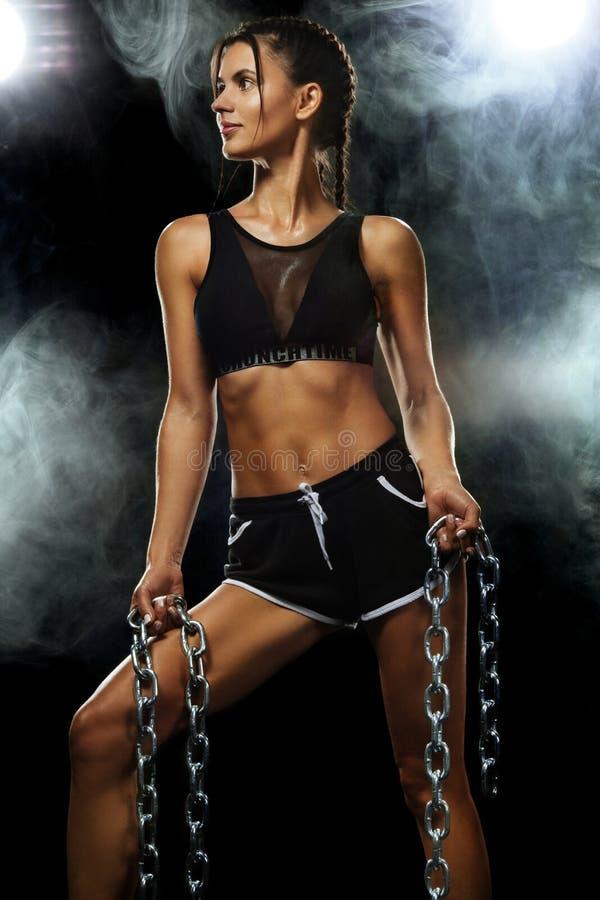 Atleta adatto della donna di sport dei giovani muscolari Allenamento con le catene su fondo nero Copi lo spazio per gli annunci d immagini stock