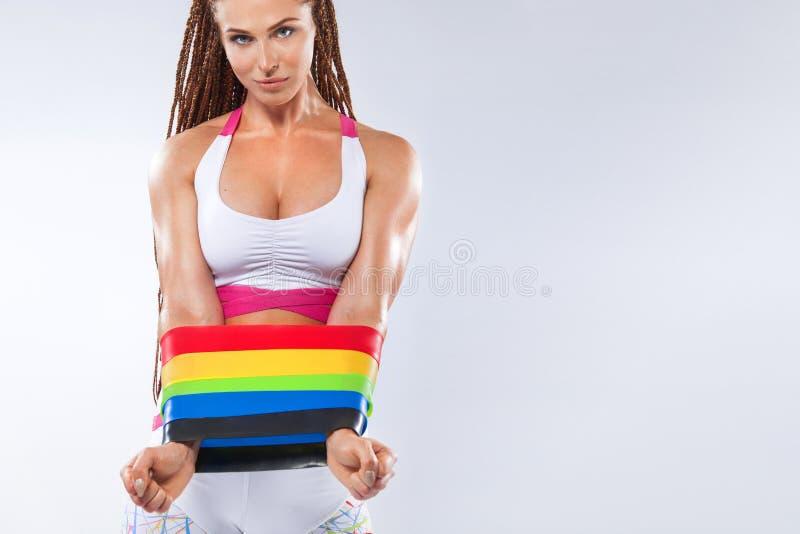 Atleta adatto della donna di sport dei giovani muscolari che mostra corredo di mini bande o estensore nella palestra Copi lo spaz immagine stock