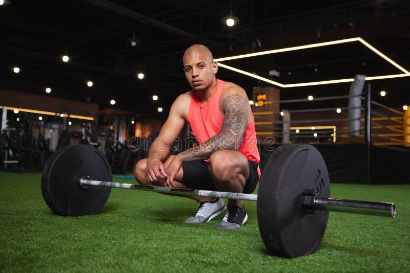 Atleta africano de sexo masculino hermoso que se resuelve en el gimnasio foto de archivo