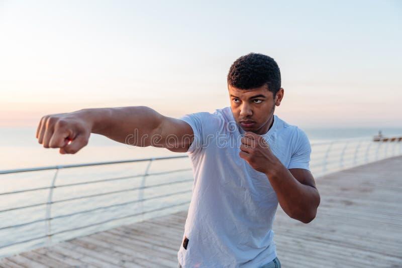 Atleta africano focalizado do homem que dá certo no cais na manhã imagens de stock