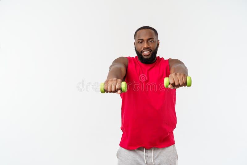 Atleta afro-americano novo Holding Lifting Dumbbells no fundo branco isolado fotos de stock