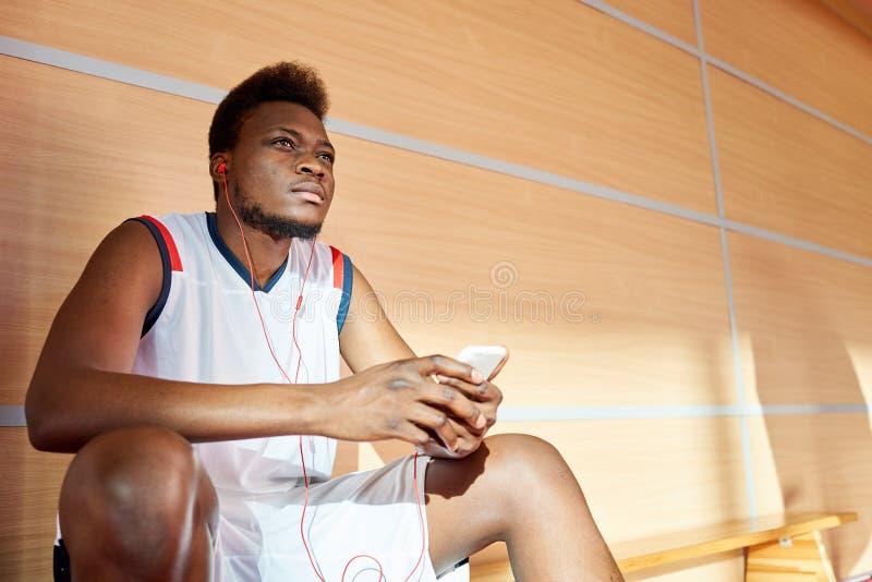 Atleta afro-americano que escuta a música no gym imagem de stock