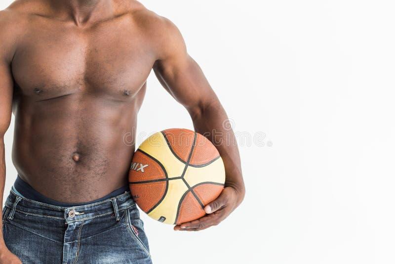 Atleta afroamericano muscolare con la palla di pallacanestro su fondo bianco immagine stock