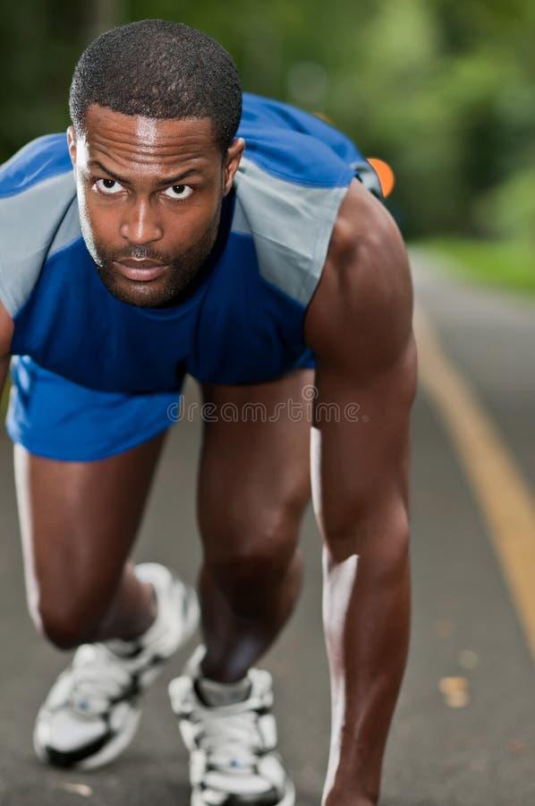 Atleta afroamericano Running On una trayectoria enselvada foto de archivo libre de regalías