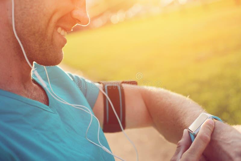 Atleta alegre que verifica seu relógio esperto no pulso fotografia de stock royalty free