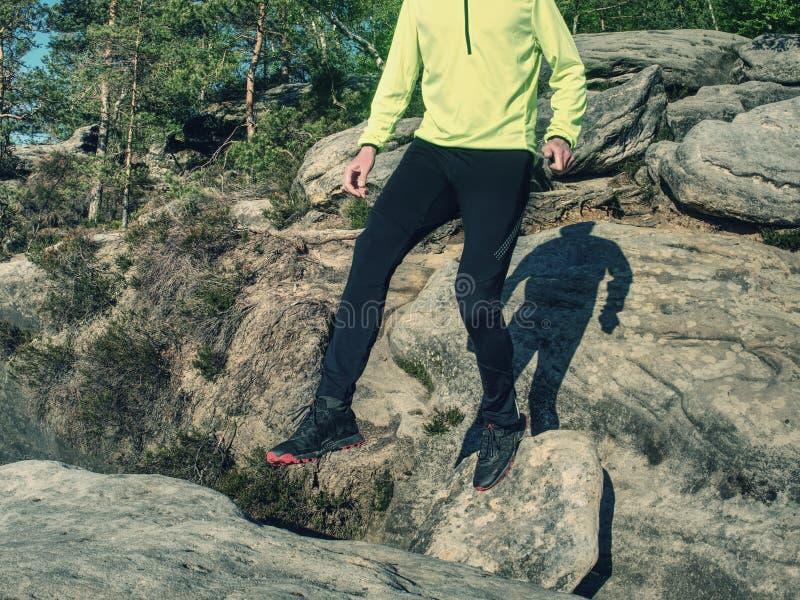 Atleta ao saltar durante uma fuga que corre nas montanhas fotografia de stock