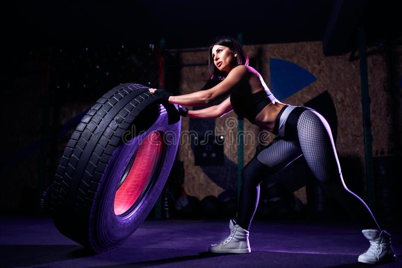 Atleta apto atractivo de la mujer de la Edad Media que se resuelve con un neumático enorme, dando vuelta y moviendo de un tirón e foto de archivo libre de regalías