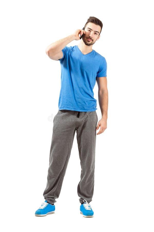 Atleta apto de los jóvenes en ropa de deportes que habla en el teléfono que mira la cámara fotos de archivo libres de regalías
