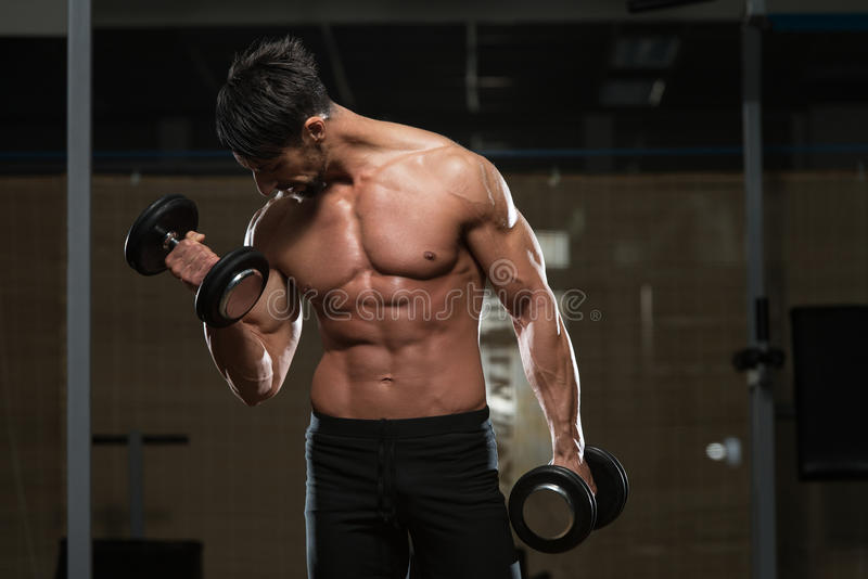 Atleta apto Exercise With Dumbbells imagens de stock royalty free