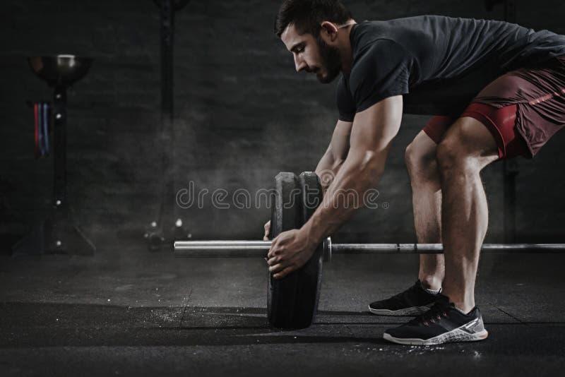 Atleta apto transversal novo que prepara o barbell para o peso de levantamento no gym Proteção da magnésia do Barbell Homem consi fotos de stock royalty free