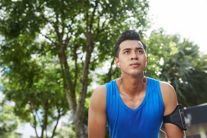 Atleta asiático sudoroso después del maratón imagen de archivo