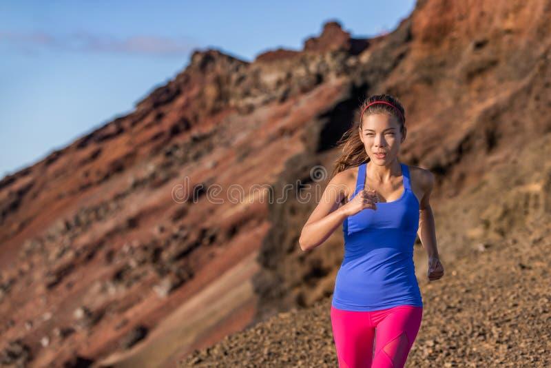 Atleta asiatico della donna del corridore della traccia che corre nel paesaggio della montagna del deserto Determinazione e motiv immagine stock